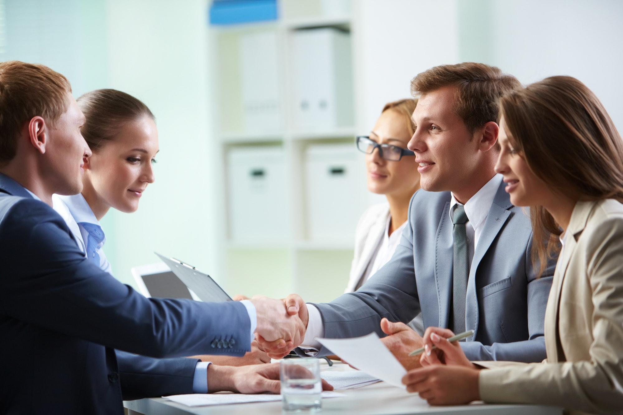 Confident businessmen handshaking at meeting